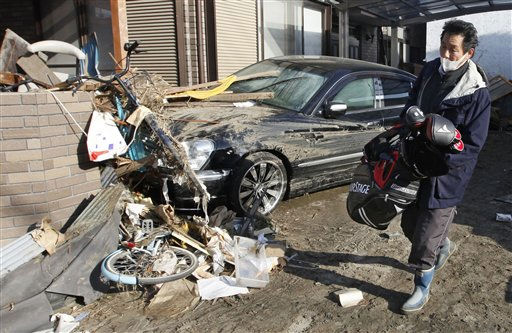 A resident of the seaside town of Yotsukura, northern Japan, carries his golf clubs as he clears debris from their home Monday, March 14, 2011, three days after a giant quake and tsunami struck the country&#39;s northeastern coast. <span class=meta>(AP Photo&#47; Mark Baker)</span>