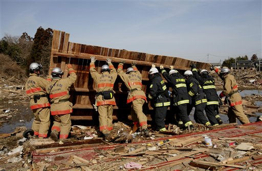 Fire department rescue workers search for victims, Monday, March 14, 2011, in the coastal area of Soma city, Fukushima prefecture, Japan, three days after a massive earthquake and tsunami struck the country&#39;s northeast coast.  <span class=meta>(AP Photo&#47; Wally Santana)</span>