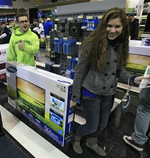 Josh Blankfeld, left to right, gives a thumbs-up as Blankfeld and Erin Burke carry a 50-inch television to the checkout at a Best Buy Friday, Nov. 23, 2012, in Mayfield Heights, Ohio.
