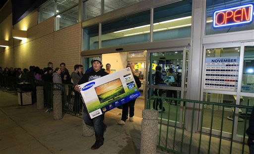 Christian Adorno, 13, walks out of a Best Buy with a 40-inch television Friday, Nov. 23, 2012, in Mayfield Heights, Ohio. The store opened at 12 a.m. on Friday.