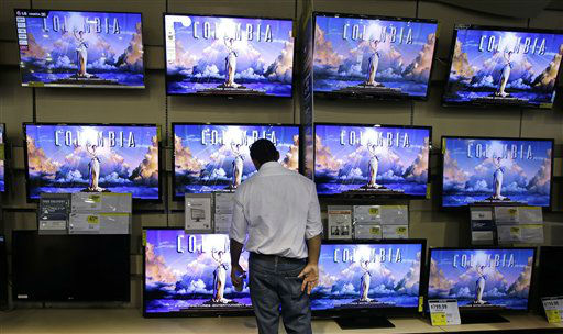 A shopper looks at televisions at a Best Buy...