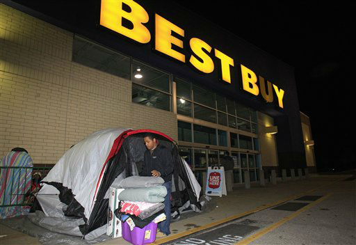 Stefan Rood, 20, folds blankets as he cleans out his tent outside a Best Buy Thursday, Nov. 22, 2012, in Mayfield Heights, Ohio. while waiting for the store to open at 12 a.m. on Friday.