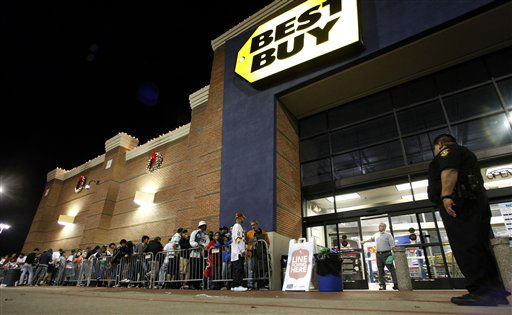 Tarrant County Sheriffs Deputy Nick Downs, right, watches a line of shoppers as Best Buy general manager Shaun Ogdie, standing at door, peers outside as he and his employees prepare to open at midnight Thursday Nov. 22, 2012, in Arlington, Texas.  <span class=meta>(AP Photo&#47; Tony Gutierrez)</span>