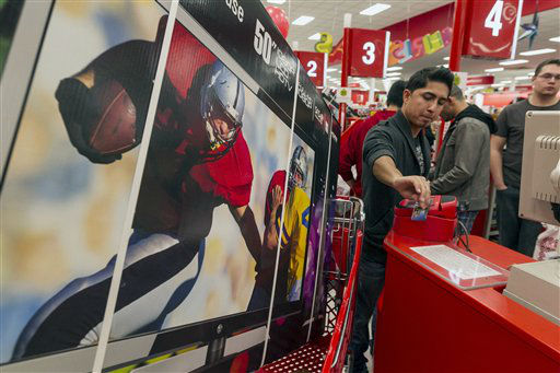 Consumer Ash Gan, 19, swipes his credit card to par for a television doorbuster deal at Target store in Burbank, Calif., on Thursday, Nov. 22, 2012.  <span class=meta>(AP Photo&#47; Damian Dovarganes)</span>