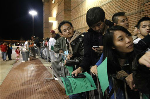 Shoppers stand in line, some holding green sale vouchers that were handed out by employees, at a Best Buy department store waiting for the store&#39;s opening at midnight for a Black Friday sale Thursday Nov. 22, 2012, in Arlington, Texas.  <span class=meta>(AP Photo&#47; Tony Gutierrez)</span>