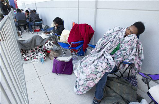An unidentified woman sits, wrapped in a blanket, outside a Pembroke Pines, Fla. Best Buy store, late Thursday, Nov. 22, 2012.  <span class=meta>(AP Photo&#47; J Pat Carter)</span>