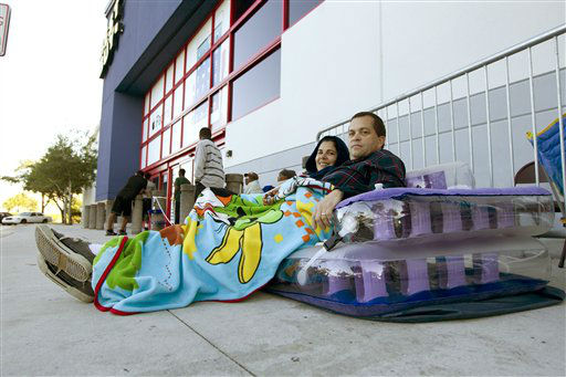 Mercy and Ozzy Dominquez try to stay warm as they wait outside a Pembroke Pines, Fla. Best Buy store, late Thursday, Nov. 22, 2012.  <span class=meta>(AP Photo&#47; J Pat Carter)</span>