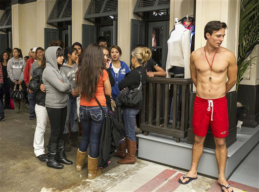 A Lifeguard model stands outside the front door of a  Hollister Co. clothing store, as consumers line up on the early morning hours Friday, Nov. 23, 2012 at the Glendale Galleria mall in Glendale, Calif.