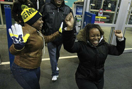 Teaje Price, left to right, 22, and Kristi Marshall, 42, celebrate as they enter a Best Buy Friday, Nov. 23, 2012, in Mayfield Heights, Ohio.