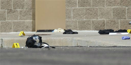 Yellow markers sit next to evidence, including a gas mask, as police investigate the scene outside the Century 16 movie theater east of the Aurora Mall in Aurora, Colo. on Friday, July 20, 2012.  <span class=meta>(AP Photo&#47; David Zalubowski)</span>