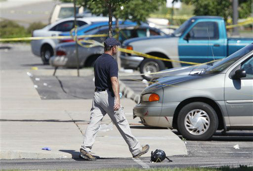 An investigator walks next to a gas mask outside the Century 16 movie theater east of the Aurora Mall in Aurora, Colo. on Friday, July 20, 2012.  <span class=meta>(AP Photo&#47; David Zalubowski)</span>