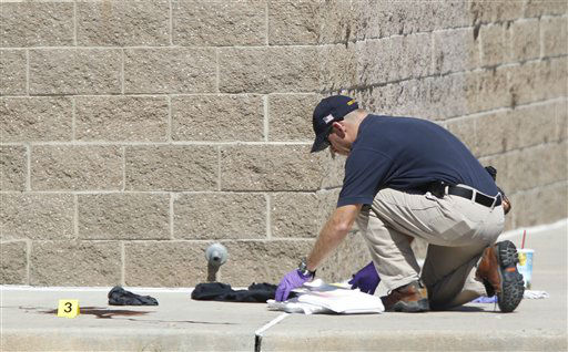 An investigator inspects evidence outside the Century 16 movie theater east of the Aurora Mall in Aurora, Colo. on Friday, July 20, 2012.  <span class=meta>(AP Photo&#47; David Zalubowski)</span>