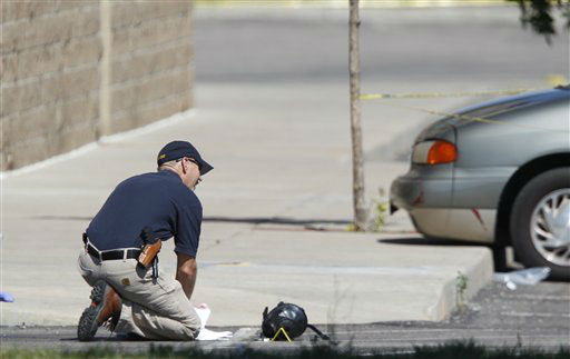 An investigator kneels next to a gas mask marked as evidence outside the Century 16 movie theater east of the Aurora Mall in Aurora, Colo. on Friday, July 20, 2012.  <span class=meta>(AP Photo&#47; David Zalubowski)</span>