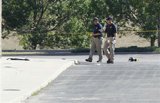 "<div class=""meta ""><span class=""caption-text "">Investigators look over evidence in parking lot at the Century 16 theatre east of the Aurora Mall in Aurora, Colo., on Friday, July 20, 2012.  (AP Photo/ David Zalubowski)</span></div>"
