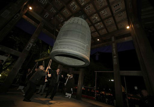 Worshipers strike a giant bell to celebrate the...