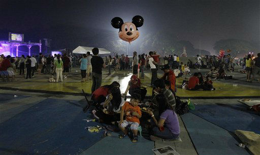 A Filipino boy holds a Mickey Mouse balloon as his family enjoys a meal during New Year celebrations at the Quezon Memorial Circle in suburban Quezon city, north of Manila, Philippines on Tuesday Jan. 1, 2013.