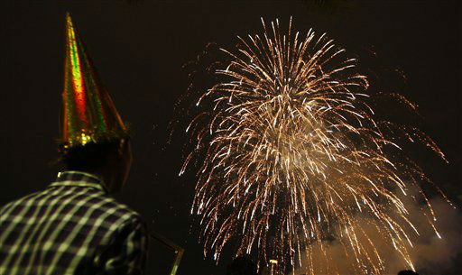 A man watches fireworks explode during New Year celebrations in Petaling Jaya, near Kuala Lumpur, Malaysia, Tuesday, Jan. 1, 2013.