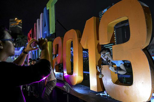 A man poses for a photo behind a giant 2013 in...