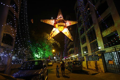 A woman with her daughter walks in a decorated street with lights to celebrate the New Year in