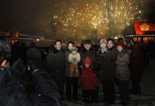 A North Korean family has their photo taken in front of fireworks as they celebrate the new year on Tuesday Jan. 1, 2013.