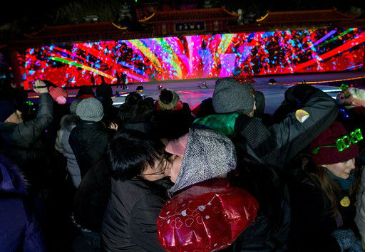 A Chinese couple kiss each other as they...