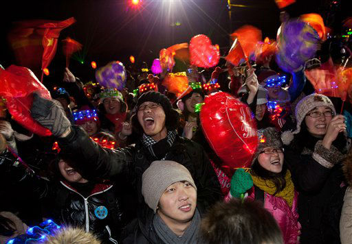 Chinese people wave national flags as they celebrate the New Year during a count-down event at the Summer Palace in Beijing Tuesday, Jan. 1, 2013. <span class=meta>(AP Photo&#47; Andy Wong)</span>