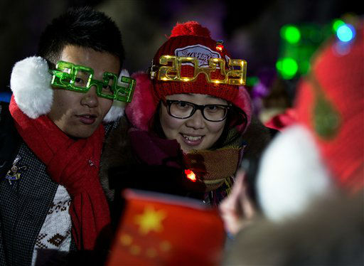A Chinese couple wearing 2013-style glasses pose for a photograph as they celebrate the new year during a count-down event at the Summer Palace in Beijing, Tuesday, Jan. 1, 2013.