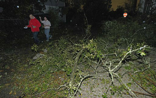 Residents walk down a street littered and partially blocked with downed tree limbs and other debris after tornado touched down Tuesday, Dec. 25, 2012 in the Midtown area of Mobile, Ala.  <span class=meta>(AP Photo&#47; G.M. Andrews)</span>