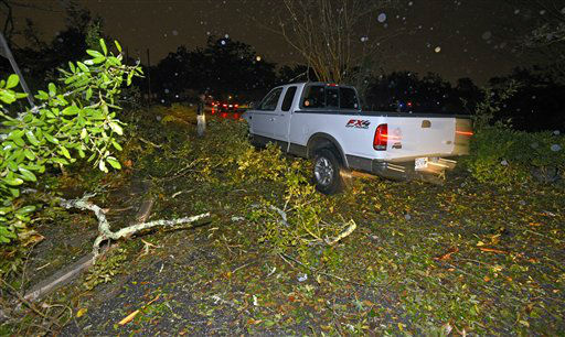 A truck tries to navigate down a street littered and partially blocked with downed tree limbs and other debris after tornado touched down Tuesday, Dec. 25, 2012 in the Midtown area of Mobile, Ala.  <span class=meta>(AP Photo&#47; G.M. Andrews)</span>
