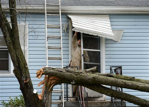 Harold Grant tries to repair his front door awning before cutting up a tree that broke in his front yard  after a tornado touched down, damaging 25 homes and knocking out power Wednesday, Jan. 30, 2013, in Ashland City, Tenn. Around 25 homes in Ashland City had minor damage.  <span class=meta>(AP Photo&#47; Mark Zaleski)</span>