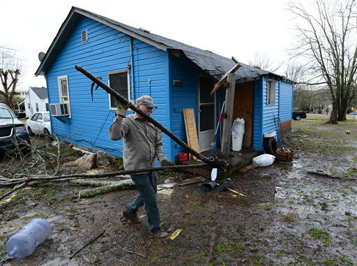 Thomas Ivey carries section of a tree he cut up after it was blown over by tornado that hit the corner of his friends house along Batson Drive Wednesday, Jan. 30, 2013, in Ashland City, Tenn. Around 25 homes in Ashland City had minor damage from the tornado. Forecasters examined the damage path of 4.6 miles Wednesday morning and estimated the peak wind speed at 115 mph, qualifying the tornado as an EF-2 twister. The path of damage was about 150 yards wide. <span class=meta>(AP Photo&#47; Mark Zaleski)</span>