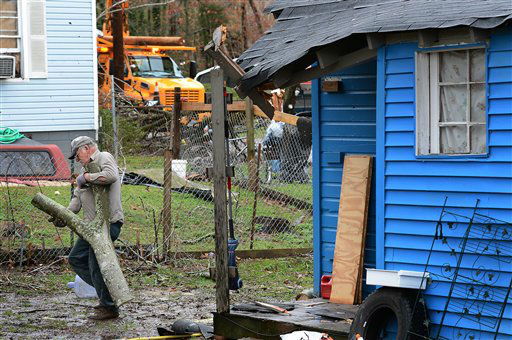 Thomas Ivey carries section of a tree he cut up after it was blown over by tornado that hit the corner of his friend&#39;s house     Wednesday, Jan. 30, 2013, in Ashland City, Tenn. Around 25 homes in Ashland City had minor damage.  <span class=meta>(AP Photo&#47; Mark Zaleski)</span>