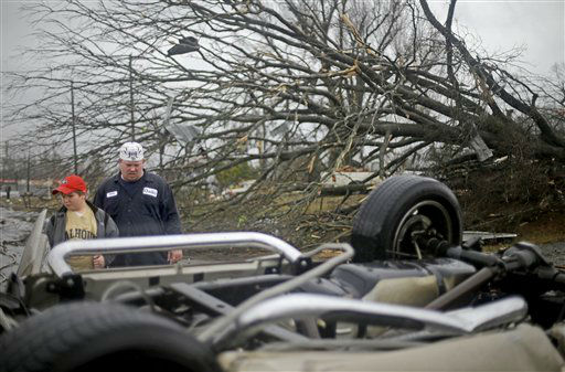 Tommy Stouffer, right, looks at his overturned car with his son Jonathan, 11, after a tornado picked it up from the parking lot where he was working across the street and dumped it in the middle of the road, Wednesday, Jan. 30, 2013, in Adairsville, Ga. A fierce storm system that roared across Georgia has left at least one person dead after it demolished buildings and flipped vehicles on Interstate 75 northwest of Atlanta.  <span class=meta>(AP Photo&#47; David Goldman)</span>