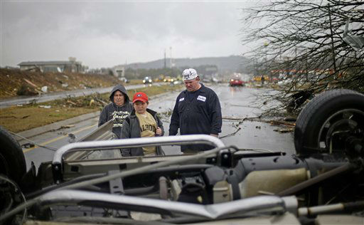 Tommy Stouffer, right, looks at his overturned car with his son Jonathan, 11, center, and wife, Norma Croft, left, after a tornado picked it up from the parking lot where he was working across the street and dumped it in the middle of the road, Wednesday, Jan. 30, 2013, in Adairsville, Ga. A fierce storm system that roared across Georgia has left at least one person dead after it demolished buildings and flipped vehicles on Interstate 75 northwest of Atlanta.  <span class=meta>(AP Photo&#47; David Goldman)</span>