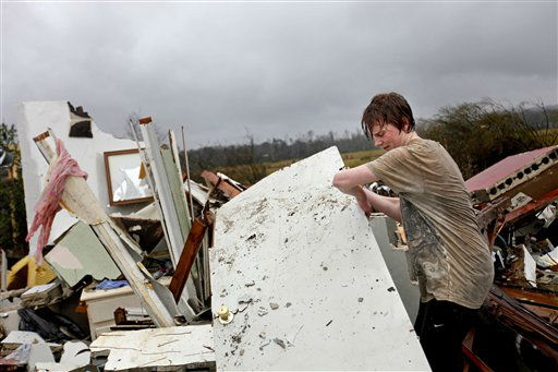 Will Carter, 15, pulls up debris while searching for the family dog, a pit bull named Niko, upon arriving to his damaged home from school following a tornado, Wednesday, Jan. 30, 2013, in Adairsville, Ga. A fierce storm system that roared across Georgia has left at least one person dead after it demolished buildings and flipped vehicles on Interstate 75 northwest of Atlanta.  <span class=meta>(AP Photo&#47; David Goldman)</span>