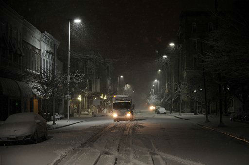 A city waste management truck drives on Broadway in Paducah, Ky. while collecting trash downtown during a winter storm Wednesday, Dec. 26, 2012.
