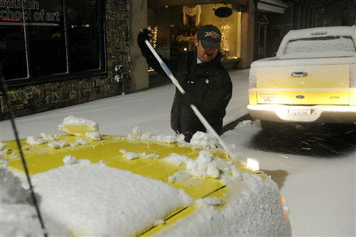 Mark Hicks of Paducah, Ky., sweeps snow off his sport utility vehicle Wednesday, Dec. 26, 2012, in Paducah, Ky.