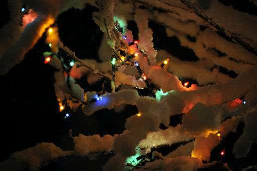 Snow rests on branches of a tree with illuminated Christmas lights during a winter storm Wednesday, Dec. 26, 2012, in Paducah, Ky.