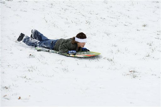 Jackson Cauley, 8, of Kevil, Ky., sleds on his belly on a hill in front of his home during a winter storm Wednesday, December 26, 2012, in Kevil, Ky.  <span class=meta>(AP Photo&#47; Stephen Lance Dennee)</span>