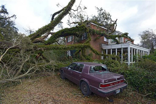 A large tree toppled by a Christmas Day tornado rests on an apartment building as residents clean up and assess the damage Wednesday, Dec. 26, 2012  in Mobile, Ala.