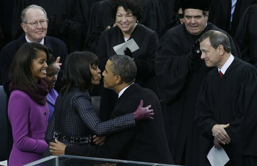 President Barack Obama kisses his wife Michelle after the ceremonial swearing-in at the U.S. Capitol during the 57th Presidential Inauguration in Washington, Monday, Jan. 21, 2013. Right is Chief Justice John Roberts.  <span class=meta>(AP Photo&#47; Paul Sancya)</span>