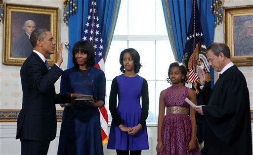 President Barack Obama takes the oath of office at the official swearing-in ceremony in the Blue Room of the White House in Washington, DC, Sunday, Jan. 20, 2013, holding the family bible is First Lady Michele Obama, administering the oath is Supreme Court Chief Justice Roberts and looking on are Obama children Sasha and Malia.  <span class=meta>(AP Photo&#47; Doug Mills)</span>