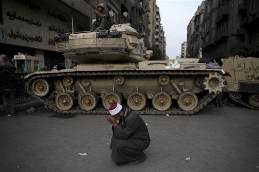 An Egyptian Muslim cleric cries in front of on army tank in Tahrir, or Liberation square, in Cairo, Egypt, Wednesday, Feb. 2, 2011. Several thousand supporters of President Hosni Mubarak, including some riding horses and camels and wielding whips, clashed with anti-government protesters Wednesday as Egypt&#39;s upheaval took a dangerous new turn. <span class=meta>(AP Photo&#47; Tara Todras-Whitehill)</span>
