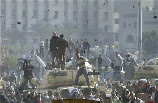 Stones fly through the air as supporters of President Hosni Mubarak, foreground , fight with anti-Mubarak protesters, rear, standing on army tanks in Cairo, Egypt, Wednesday, Feb.2, 2011. Several thousand supporters of  Mubarak, including some riding horses and camels and wielding whips, clashed with anti-government protesters Wednesday as Egypt&#39;s upheaval took a dangerous new turn. <span class=meta>(AP Photo&#47; Ahmed Ali)</span>
