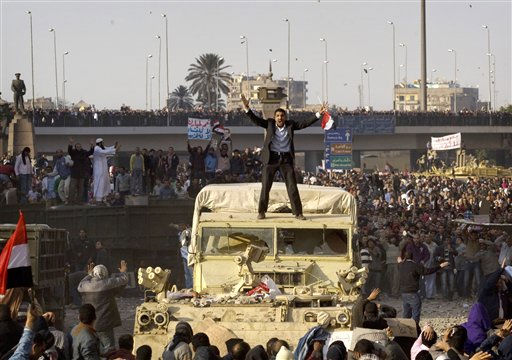 A demonstrator atop a military vehicle tries to calm the crowd, as pro-government demonstrators clash with anti-government protestors during a demonstration in Cairo, Egypt, Wednesday, Feb.2, 2011. Several thousand supporters of President Hosni Mubarak, including some riding horses and camels and wielding whips, clashed with anti-government protesters as Egypt&#39;s upheaval took a dangerous new turn. In chaotic scenes, the two sides pelted each other with stones, and protesters dragged riders off their horses.  <span class=meta>(AP Photo&#47; Sebastian Scheiner)</span>