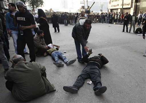 Injured anti-government protesters lie on the ground near army vehicles as they wait to be treated by medics during clashes in Tahrir, or Liberation square, in Cairo, Egypt, Wednesday, Feb. 2, 2011. Several thousand supporters of President Hosni Mubarak, including some riding horses and camels and wielding whips, clashed with anti-government protesters Wednesday as Egypt&#39;s upheaval took a dangerous new turn. <span class=meta>(AP Photo&#47; Tara Todras-Whitehill)</span>