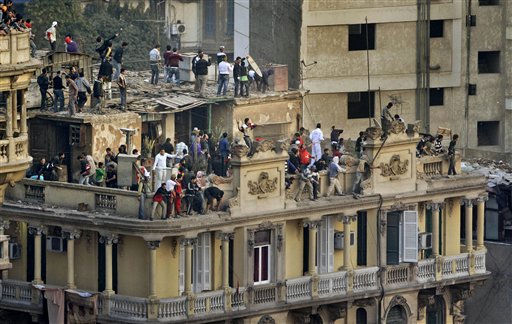 Pro-government demonstrators take to the rooftops to throw rocks down at anti-government demonstrators below, unseen, opposite the Egyptian Museum in Tahrir square in Cairo, Egypt Wednesday, Feb. 2, 2011.  <span class=meta>(AP Photo&#47; Ben Curtis)</span>