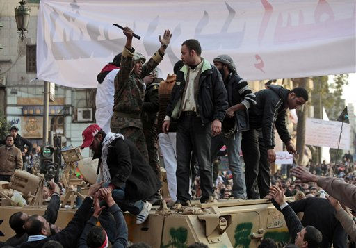 An Egyptian army officer atop an armored personnel carrier, tries to calm down anti-government demonstrators during clashes with pro-government protesters in Tahrir square, in Cairo, Egypt, Wednesday, Feb. 2, 2011. Thousands of supporters and opponents of Egyptian President Hosni Mubarak battled in Cairo&#39;s main square, raining stones, bottles and firebombs on each other in scenes of uncontrolled violence as soldiers stood by without intervening. Government backers galloped in on horses and camels, only to be dragged to the ground and beaten bloody.  <span class=meta>(AP Photo&#47; Lefteris Pitarakis)</span>