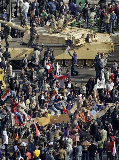 Pro-government demonstrators riding camels and carrying sticks pass by an Egyptian Army tank on their way to charge at anti-government demonstrators, unseen, near the Egyptian Museum in Tahrir square, the center of anti-government demonstrations, in Cairo, Egypt Wednesday, Feb. 2, 2011.  <span class=meta>(AP Photo&#47; Ben Curtis)</span>