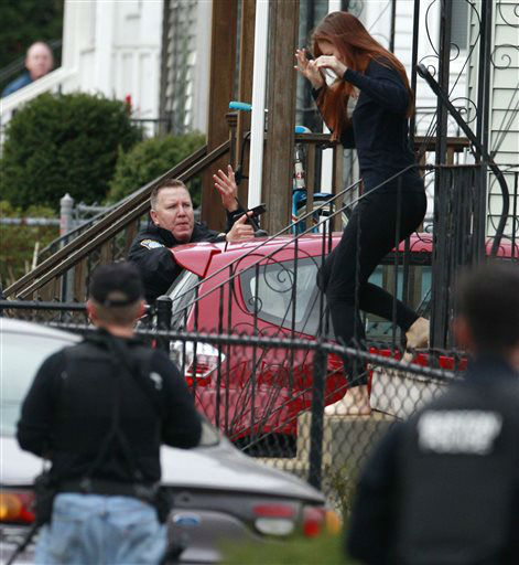 A barefooted woman runs for cover as police surround a home while searching for a suspect in the Boston Marathon bombings in Watertown, Mass., Friday, April 19, 2013.   <span class=meta>(AP Photo&#47; Charles Krupa)</span>
